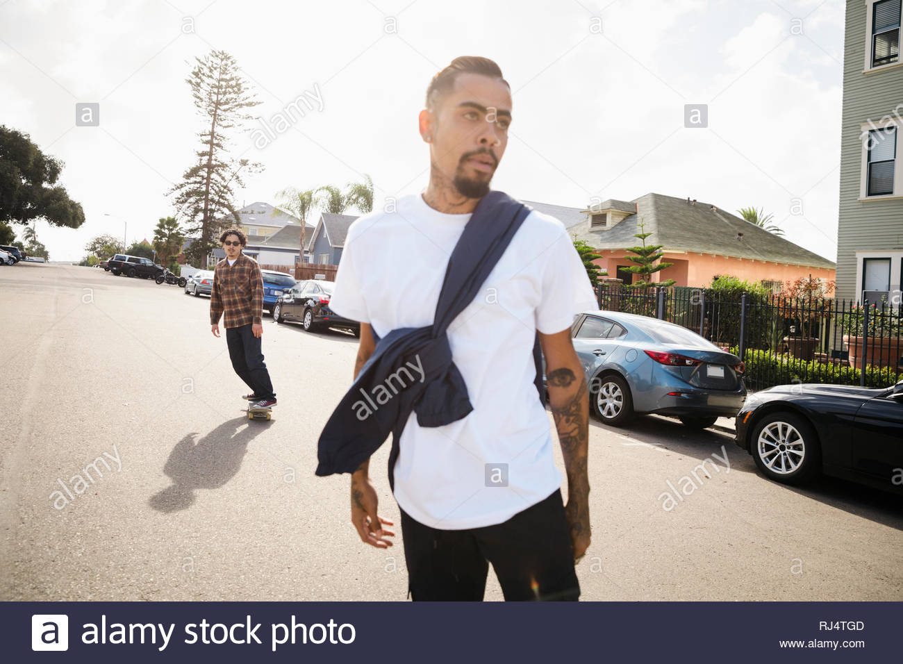 Latinx young men skateboarding on sunny street Stock Photo