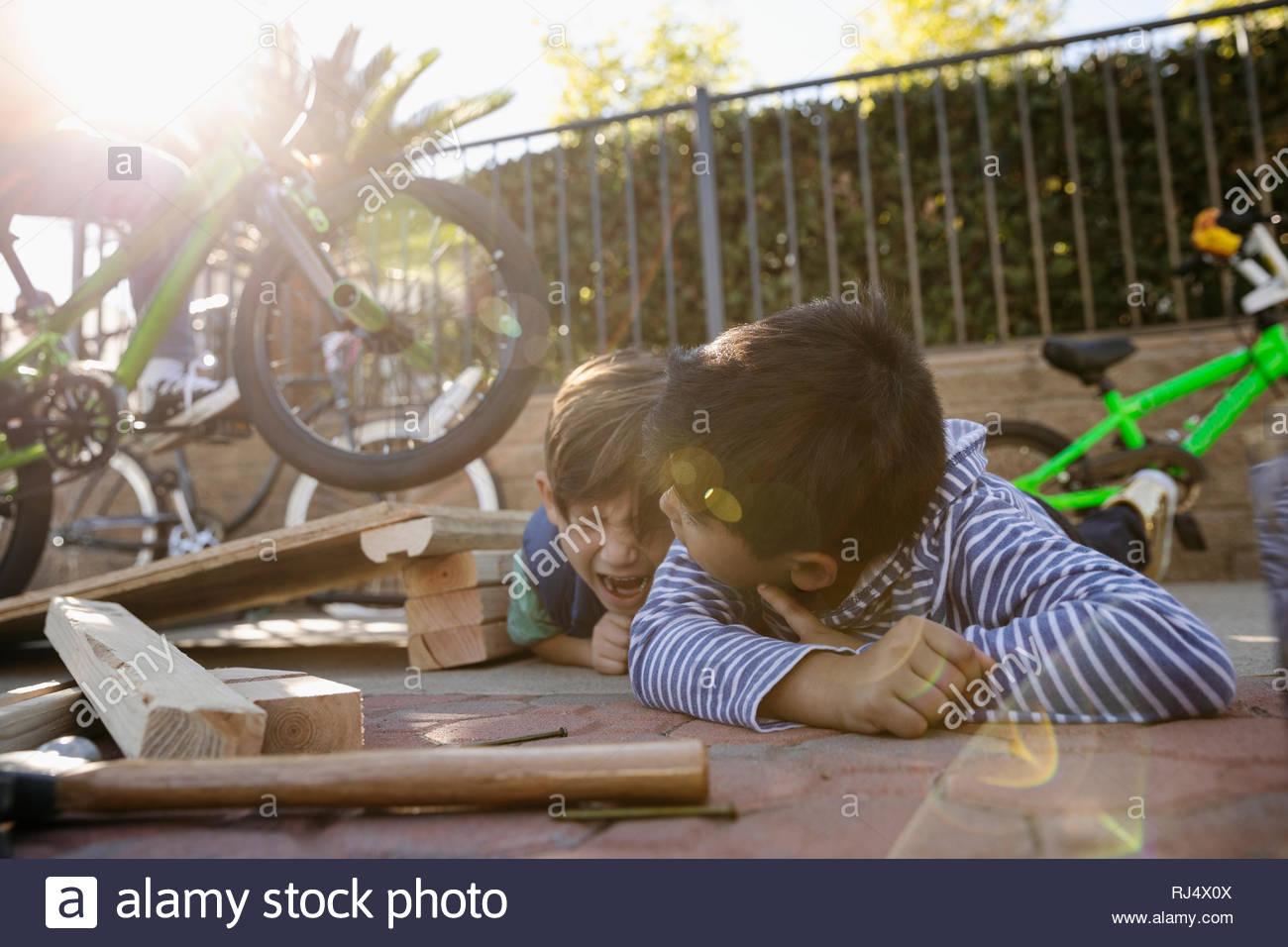 Latinx boys playing with bike ramp - Stock Image