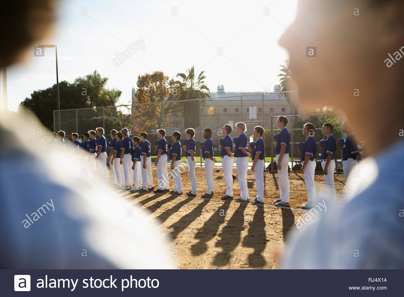 Baseball players standing in a row for national anthem - Stock Image