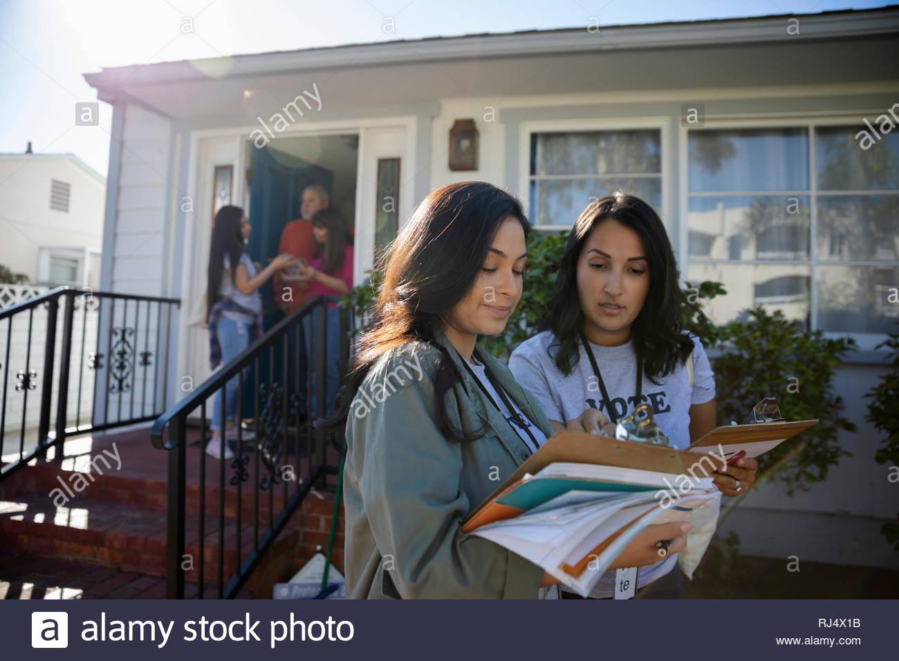 Latinx female volunteers with clipboards canvassing door-to-door in neighborhood - Stock Image