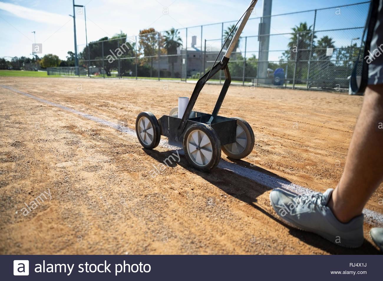 Man lining sunny baseball field - Stock Image