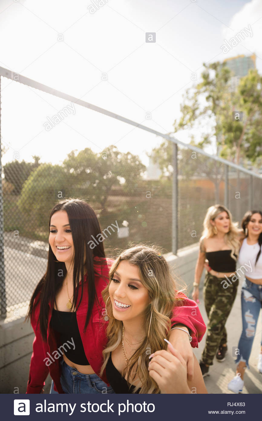 Happy Latinx young women friends walking along urban overpass fence - Stock Image