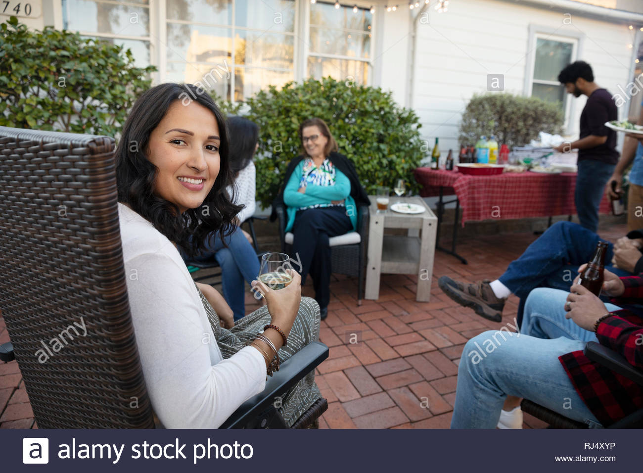 Portrait smiling Latinx woman drinking wine with family on patio - Stock Image