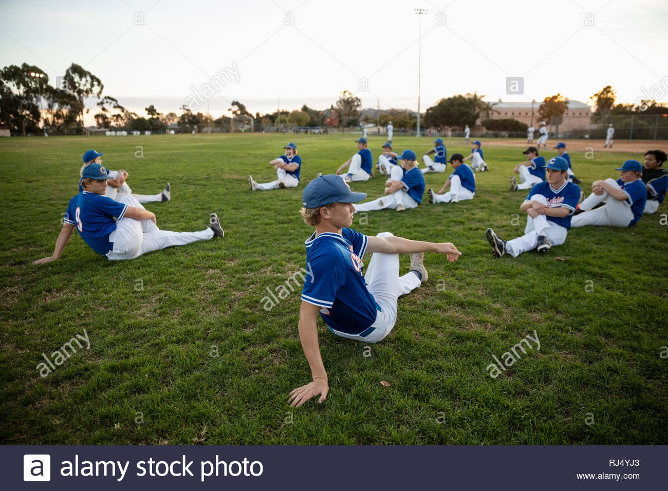 Baseball players stretching before game in grass - Stock Image