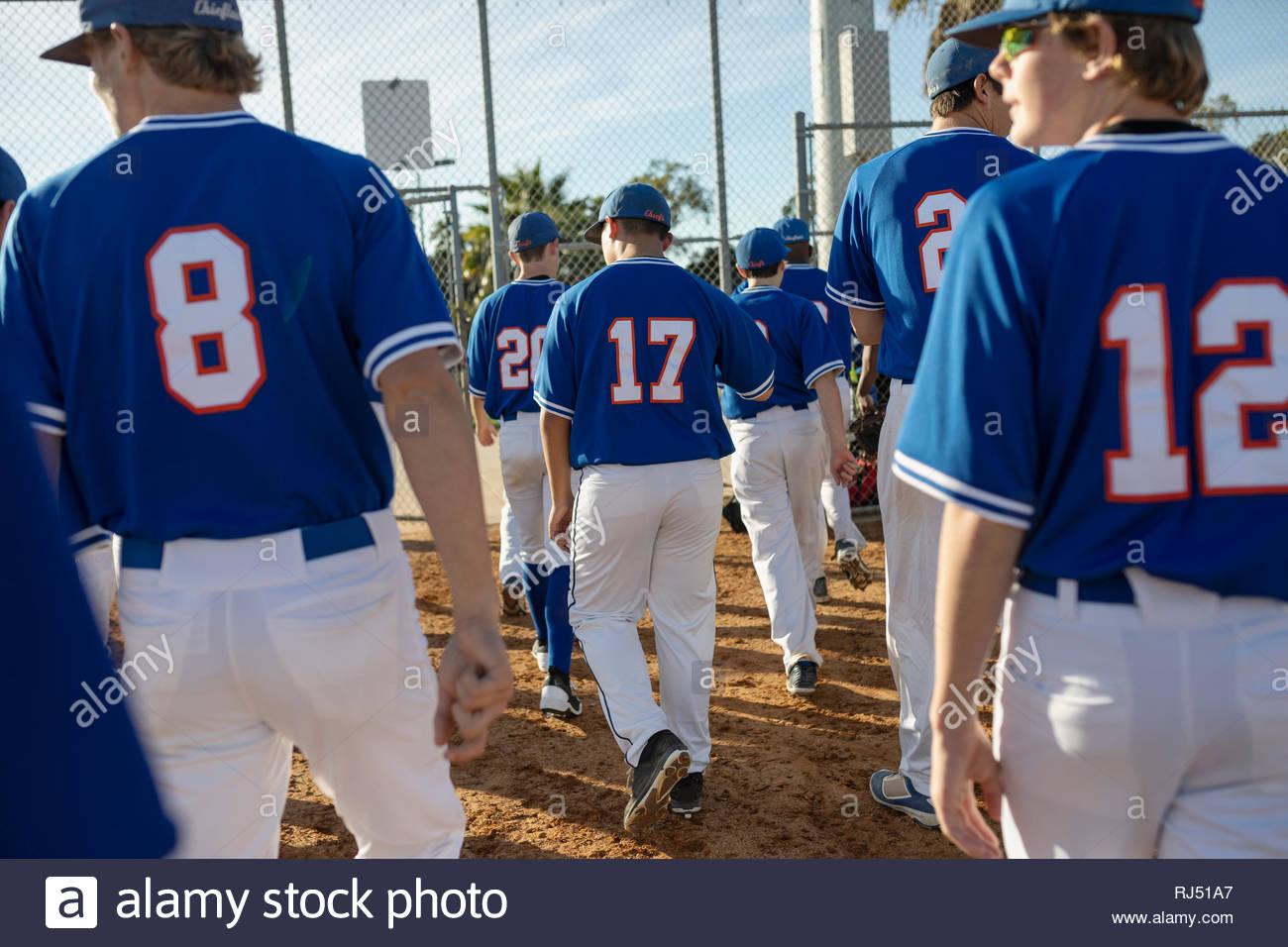Baseball players walking onto field - Stock Image