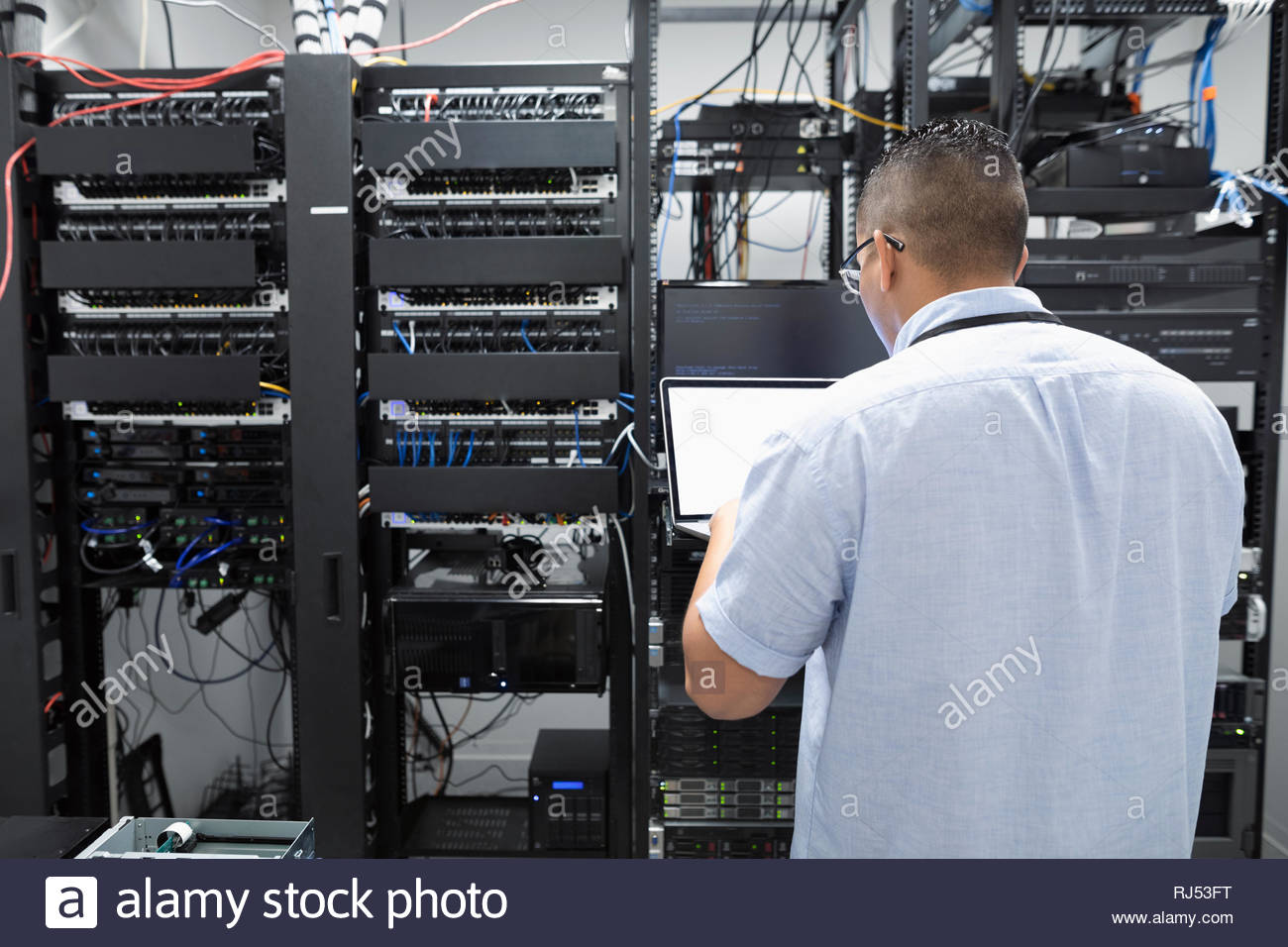 IT technician using laptop in server room - Stock Image