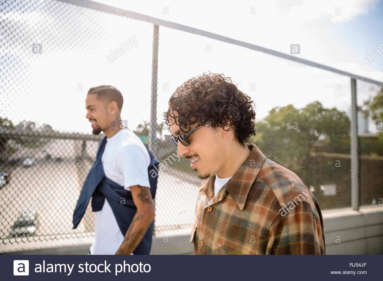 Latinx men friends walking on sunny overpass - Stock Image