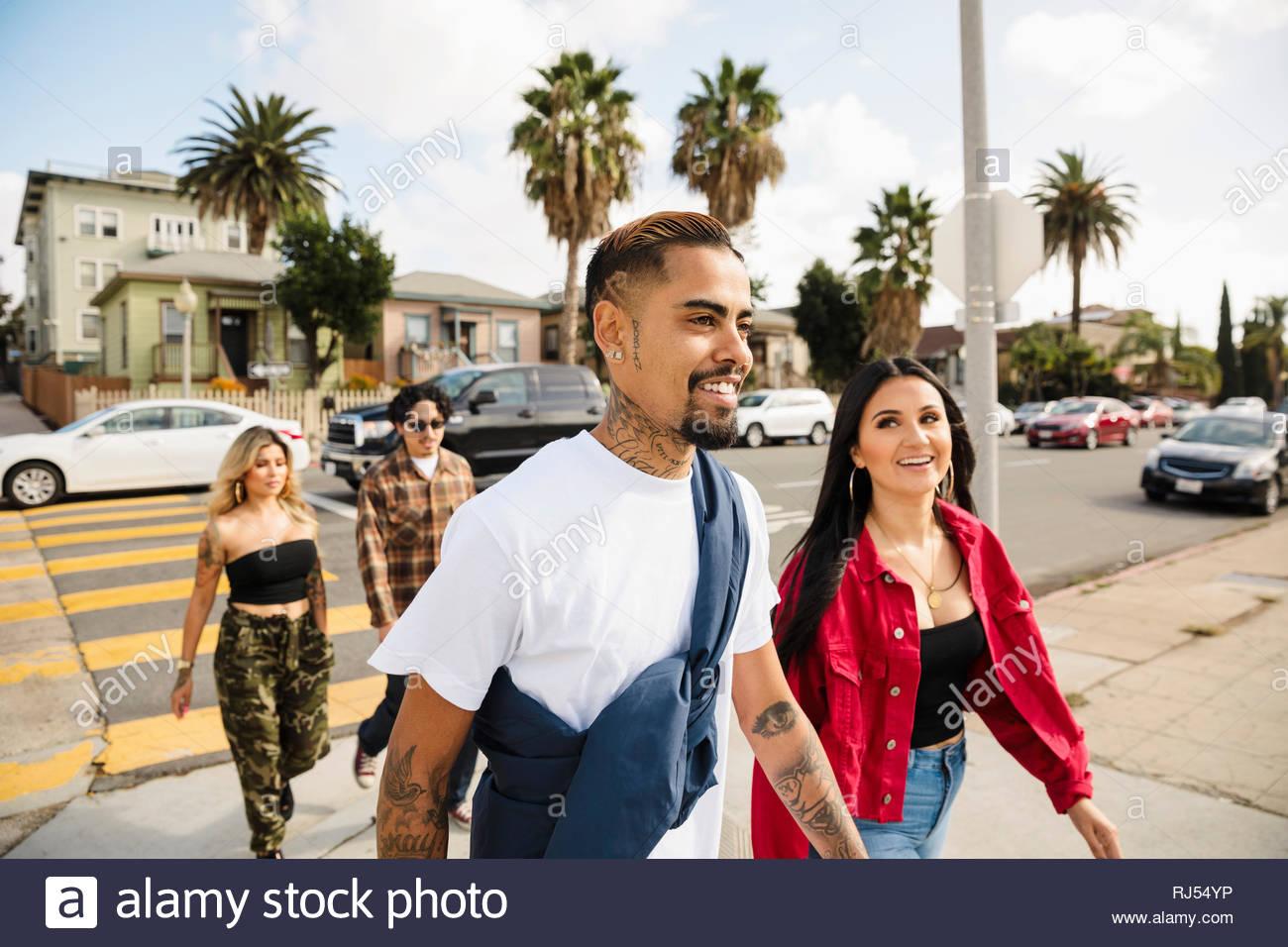 Latinx friends walking in neighborhood - Stock Image