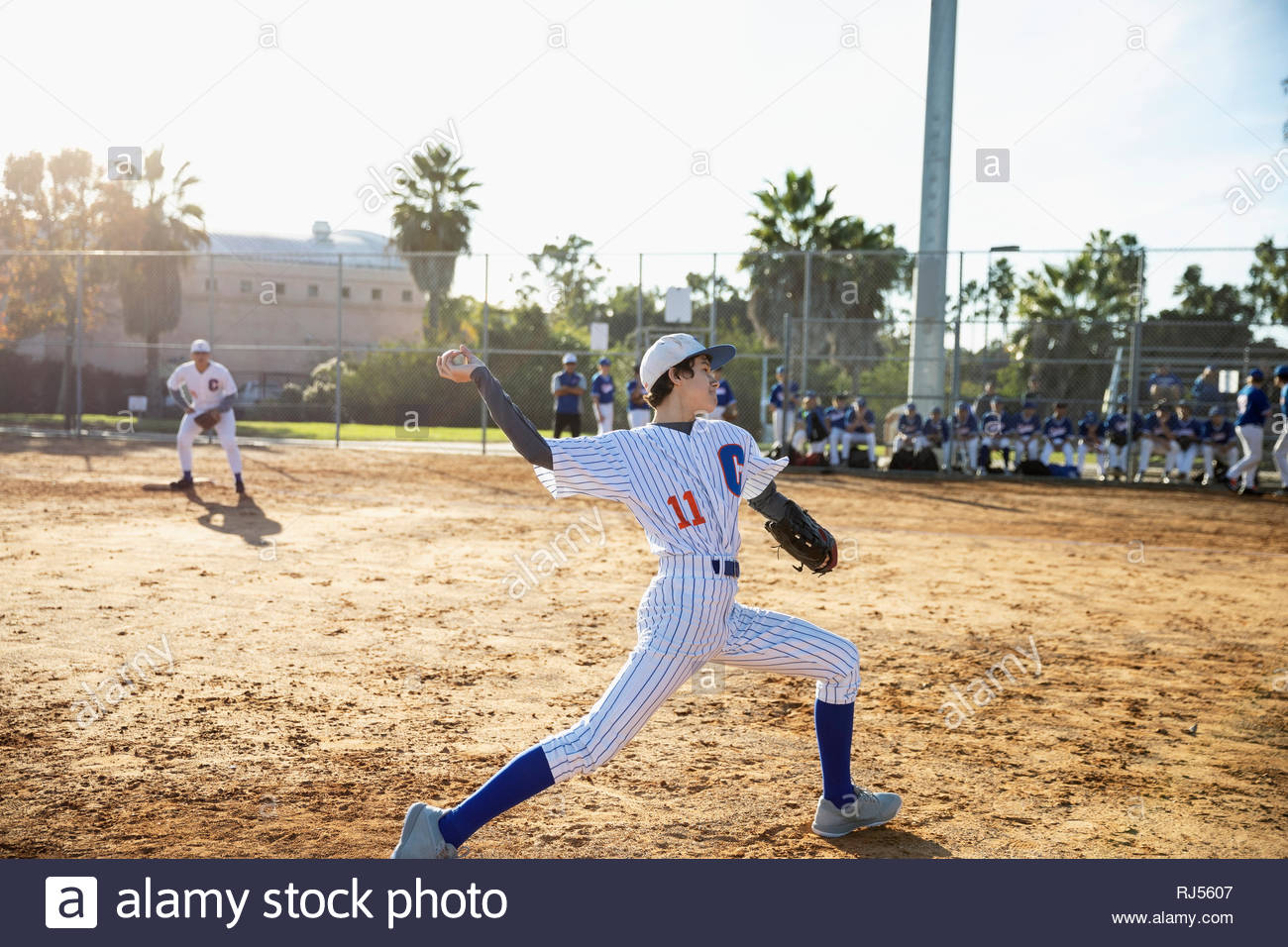 Baseball pitcher throwing the ball on sunny field - Stock Image