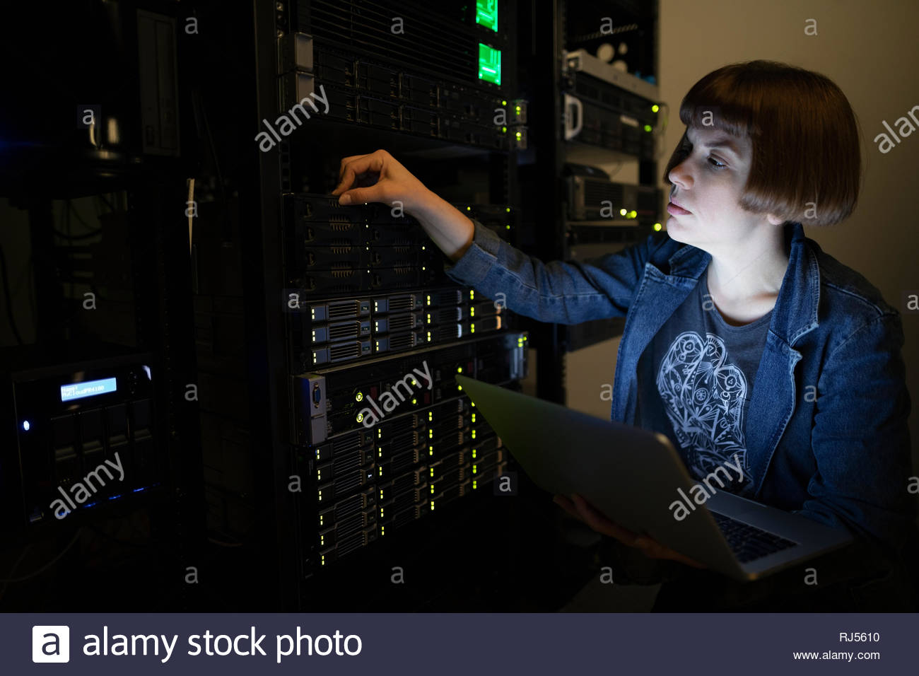 Female IT technician with laptop in server room - Stock Image