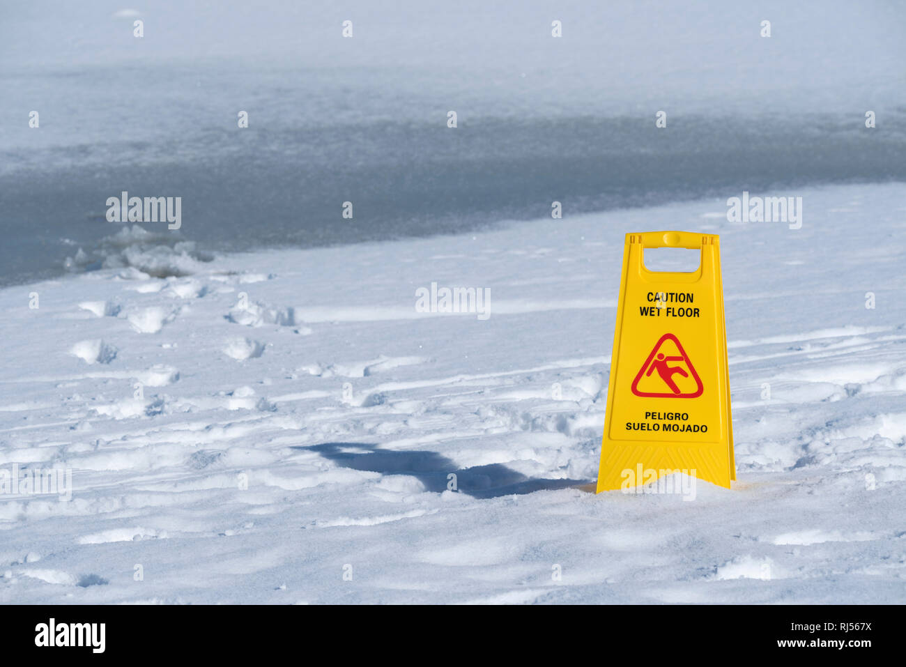 One yellow sign board caution wet floor over a frozen lake Horizontal. Selective focus - Stock Image