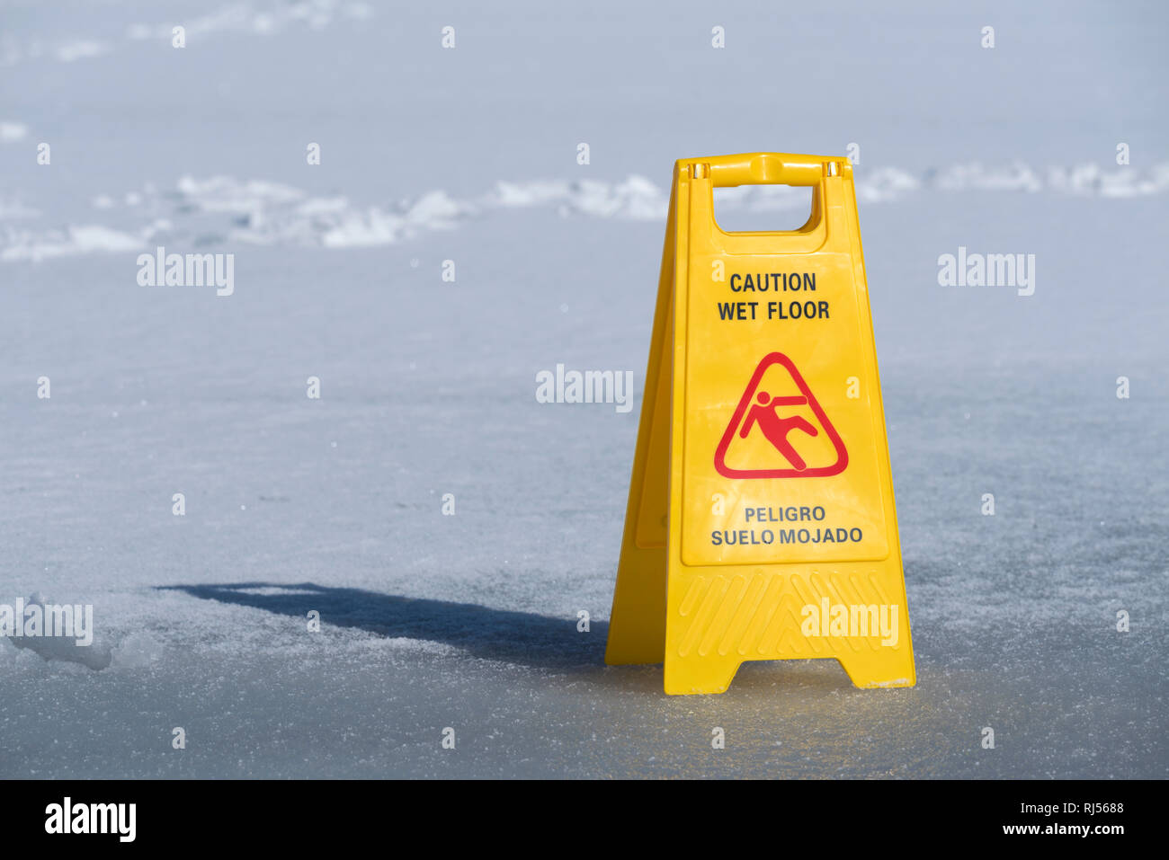 One yellow sign board caution wet floor over a frozen lake. Selective focus - Stock Image