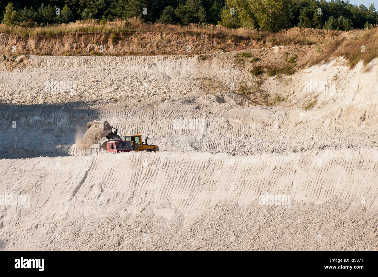 Chalk mine pit landscape in Mielnik, Poland, podlaskie, Digger heaping chalk on heavy goods vehicle, White chalk pit in open air and woods afar, nobod - Stock Image