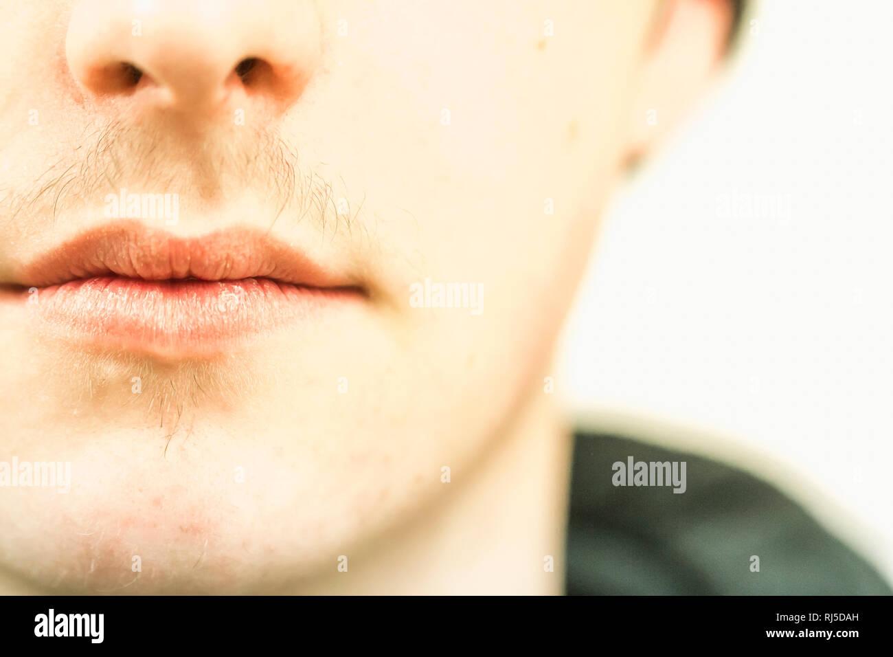 Der Mund eines jungen Mannes mit Flaum über der Oberlippe - Stock Image