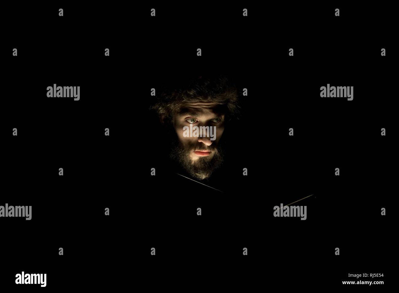 Mann mit Bart, dunkel, Gesicht beleuchtet, Portrait - Stock Image