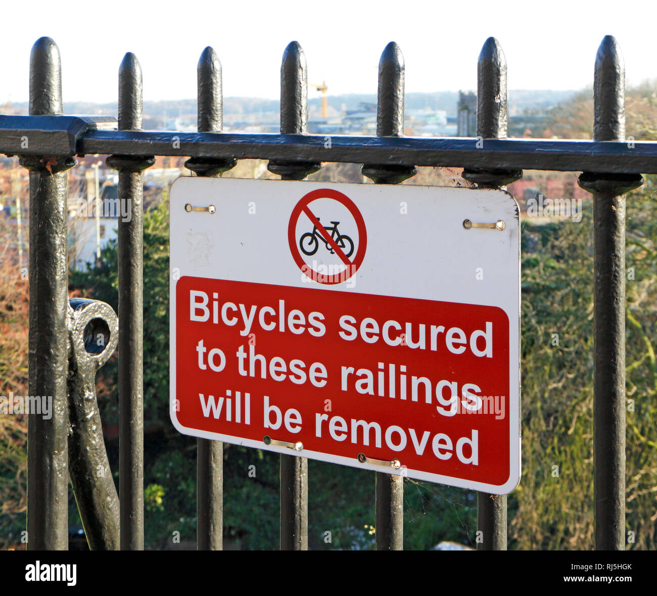 Warning notice that Bicycles secured to these railings will be removed on the Castle mound at Norwich, Norfolk, England, United Kingdom, Europe. - Stock Image