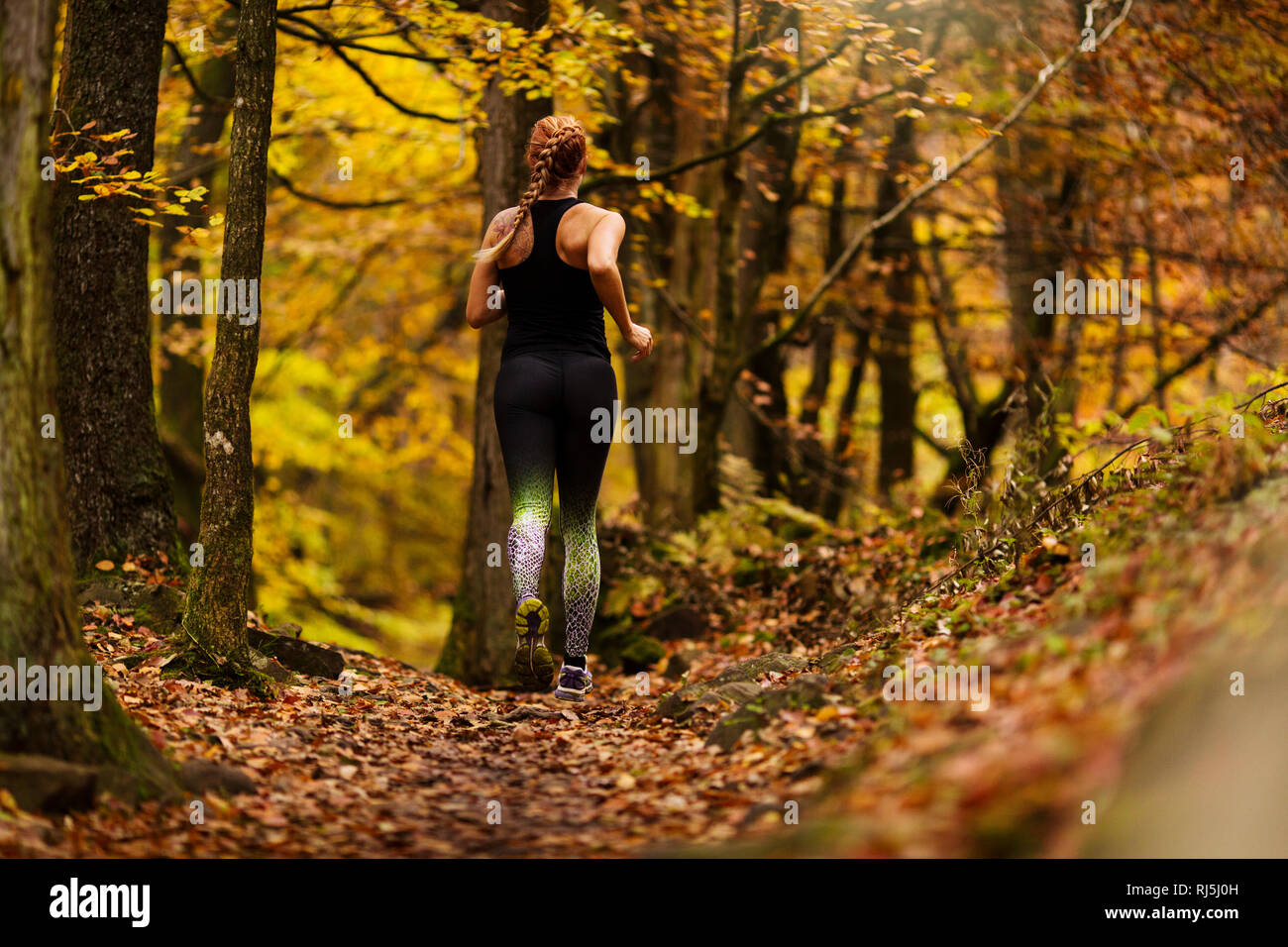 Young woman running in forest Stock Photo