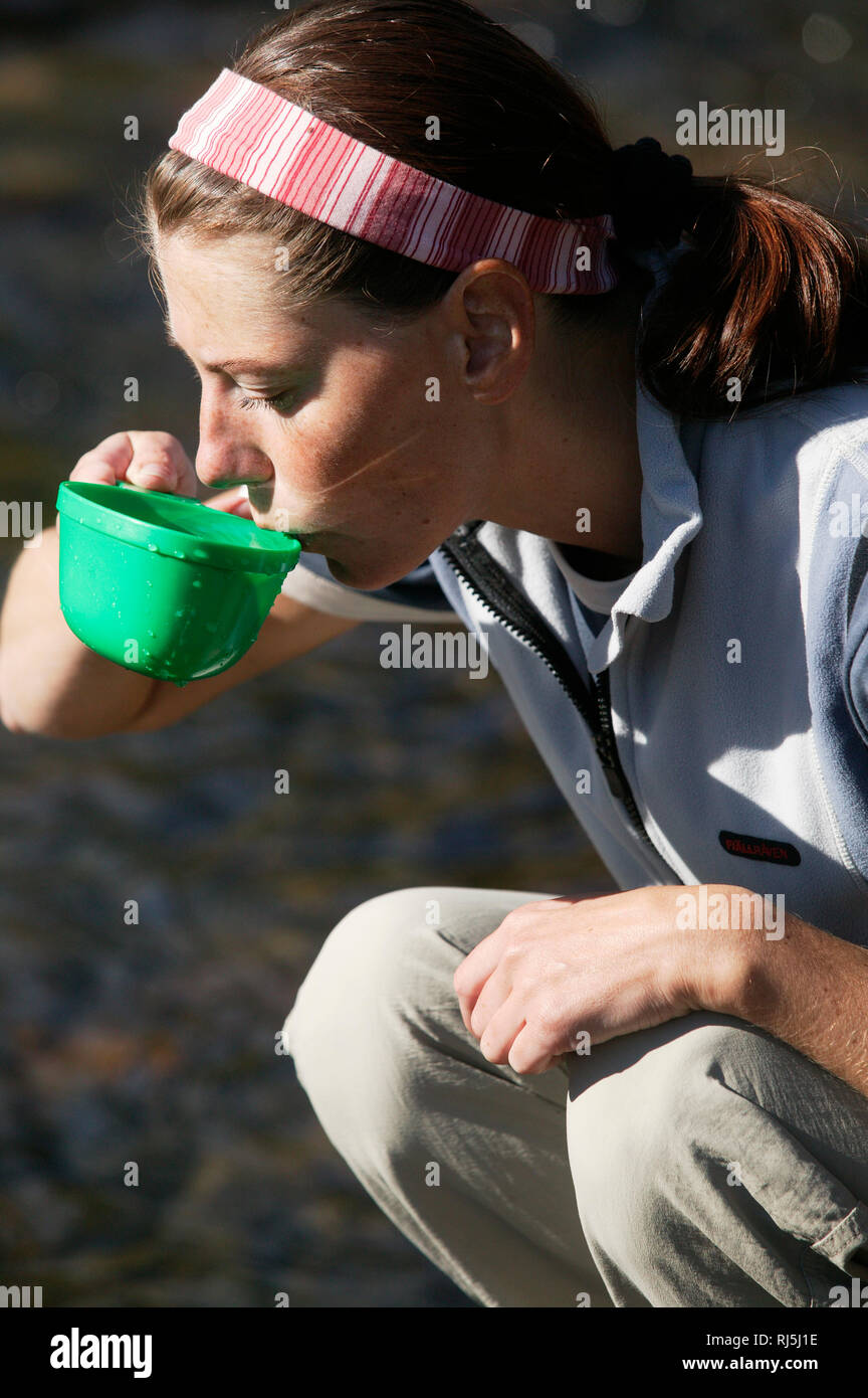 Woman drinking out of a cup Stock Photo