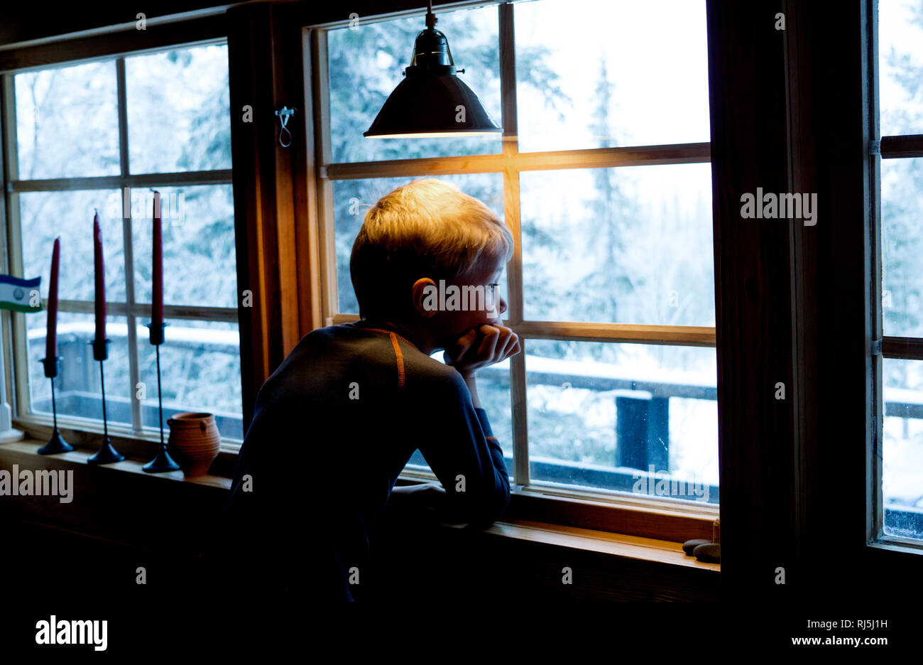 Boy looking out of a window Stock Photo