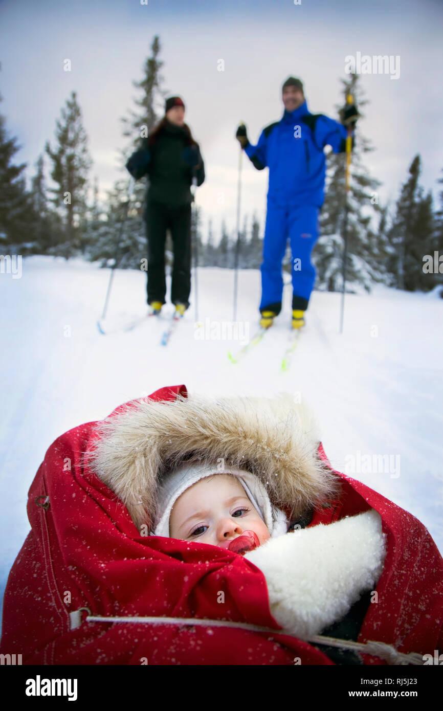 Couple skiing with baby Stock Photo