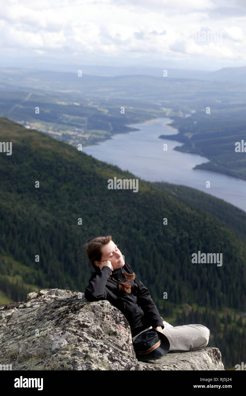 Woman sitting on a cliff Stock Photo