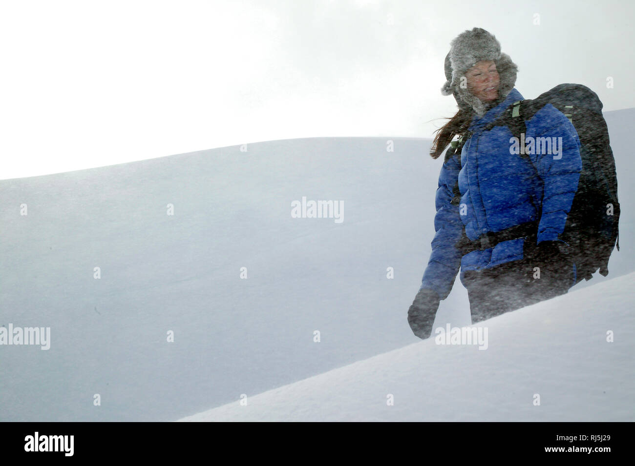 A woman walking in a snowstorm Stock Photo