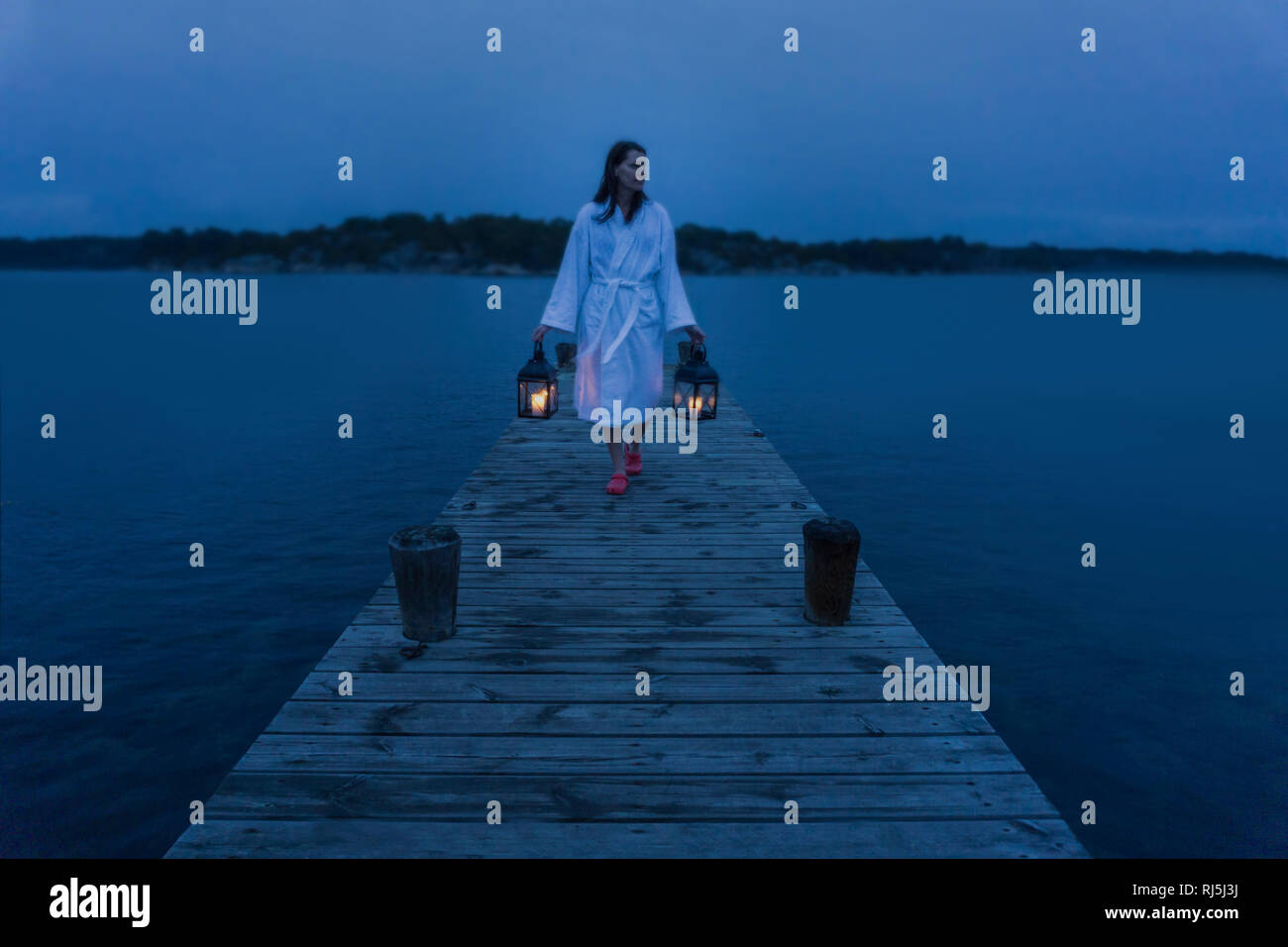 A woman with lantern on jetty Stock Photo
