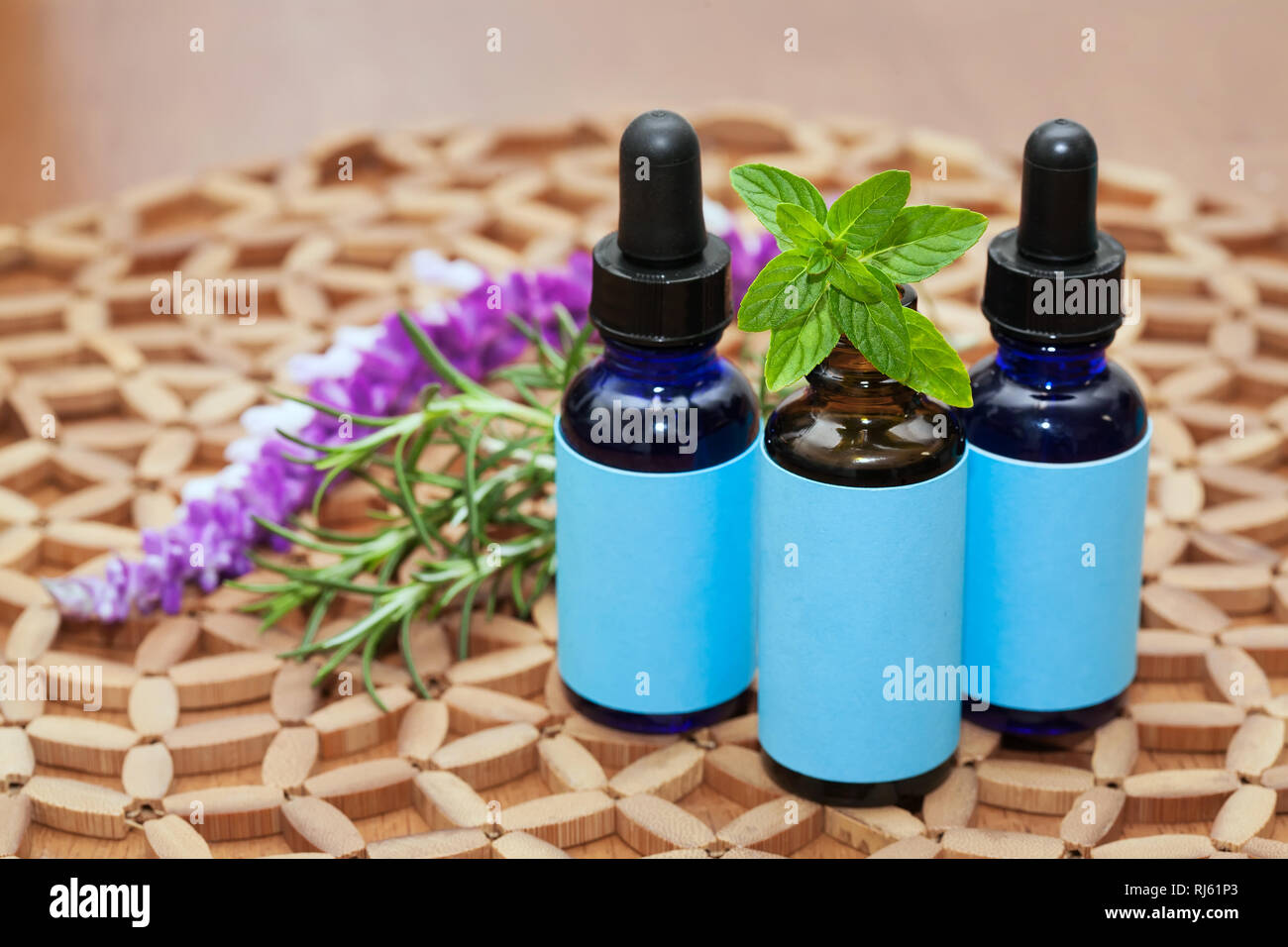Alternative or naturopathic medicine treatment in three glass bottles with droppers, mint, lavender and rosemary plants. - Stock Image
