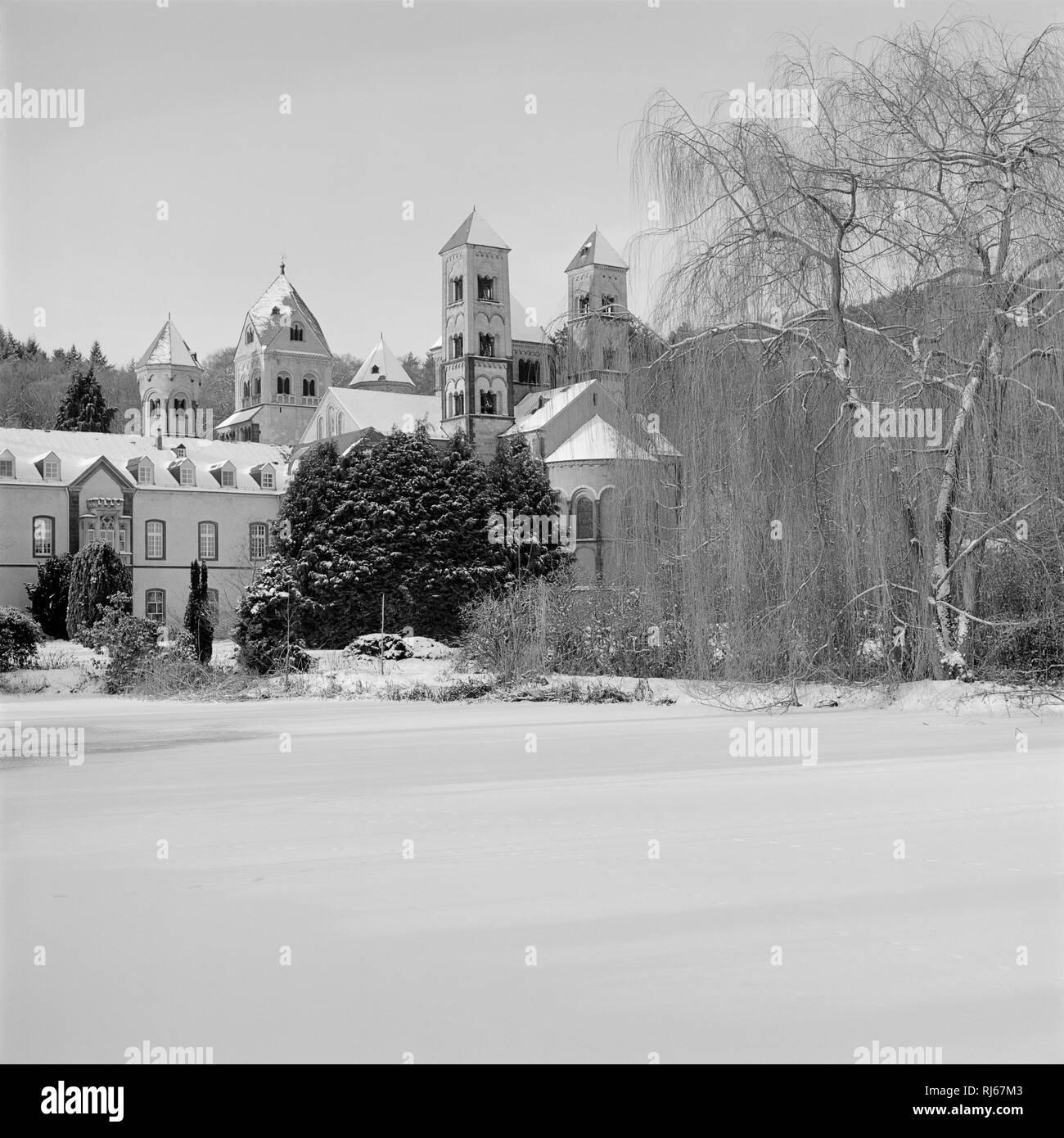 Europa, Deutschland, Rheinland-Pfalz, Kloster Maria Laach, Blick von Südosten auf Stiftskirche und Wohngebäude, davor der zugefrorenen Teich, - Stock Image