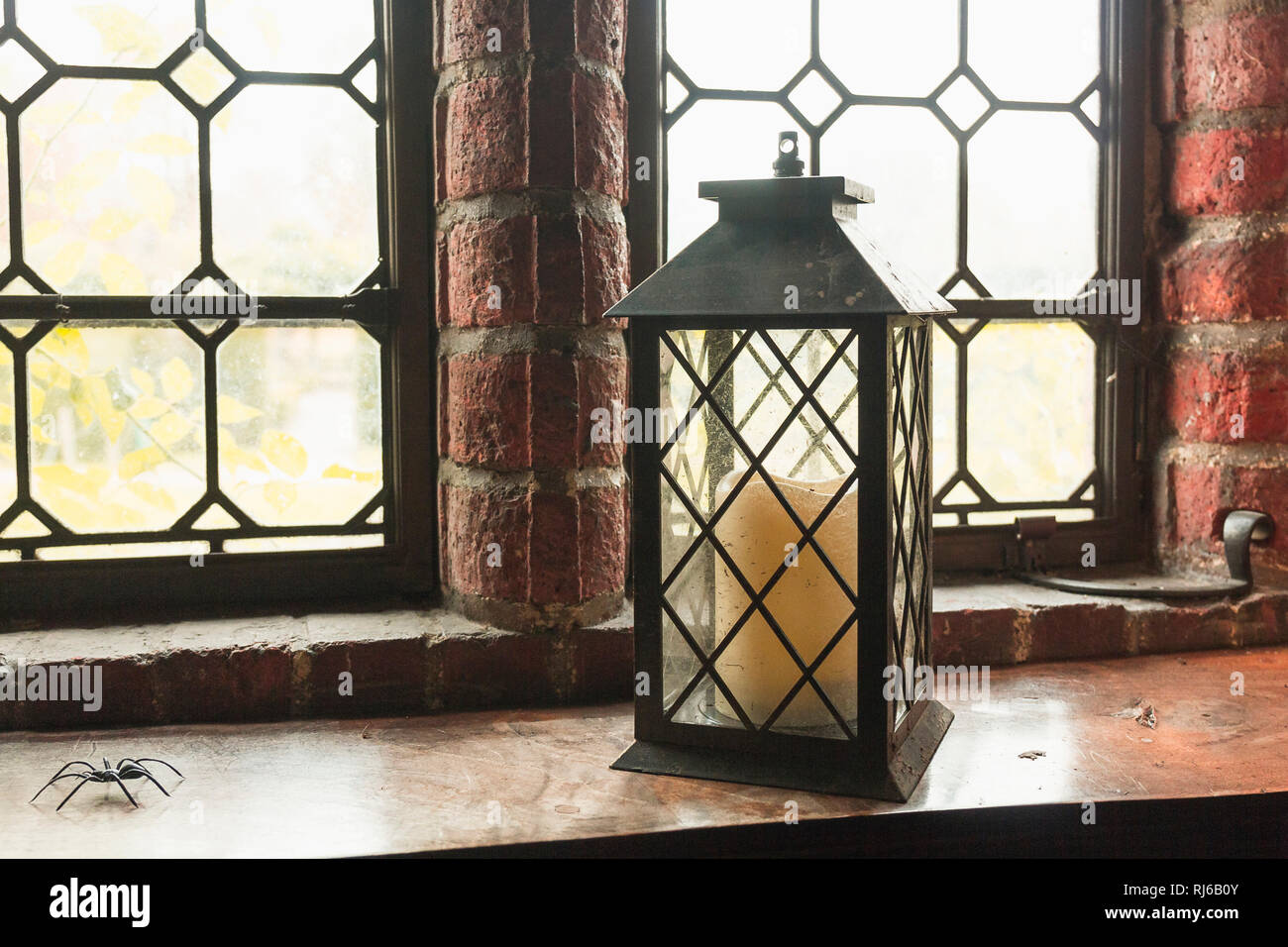 Alte Laterne mit einer Kerze steht vor einem mittelalterlichen Fenster, - Stock Image