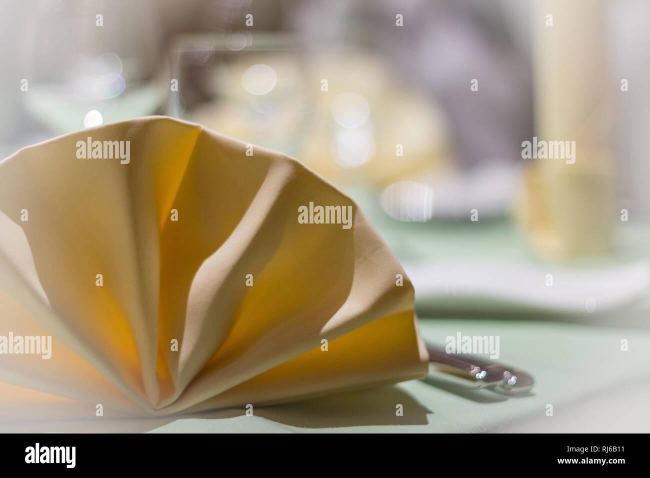 Eine gefaltete Stoffserviette auf einem gedeckten Tisch, Detailaufnahme - Stock Image