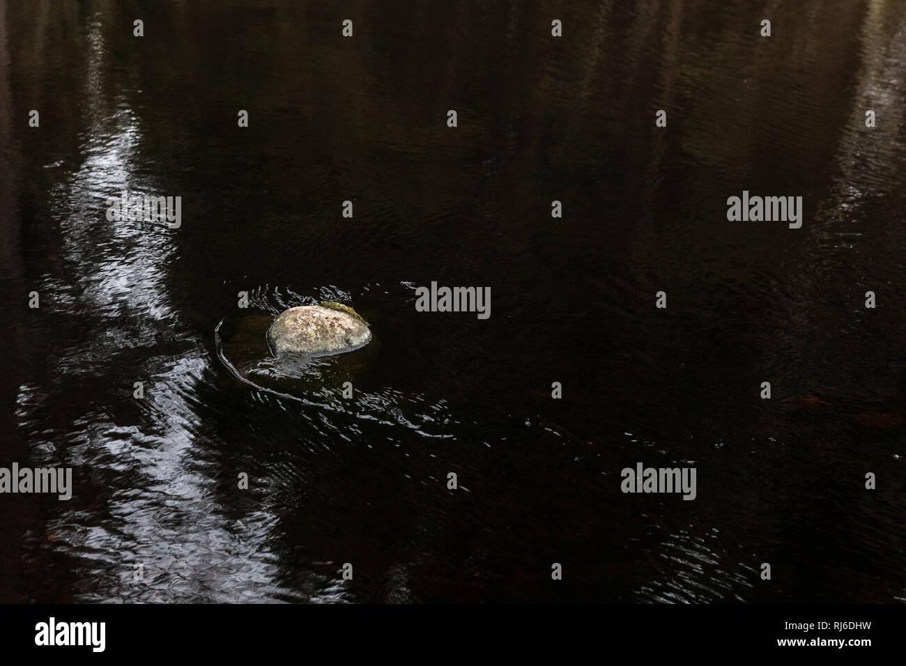 einzelner Stein im dunklen Wasser - Stock Image