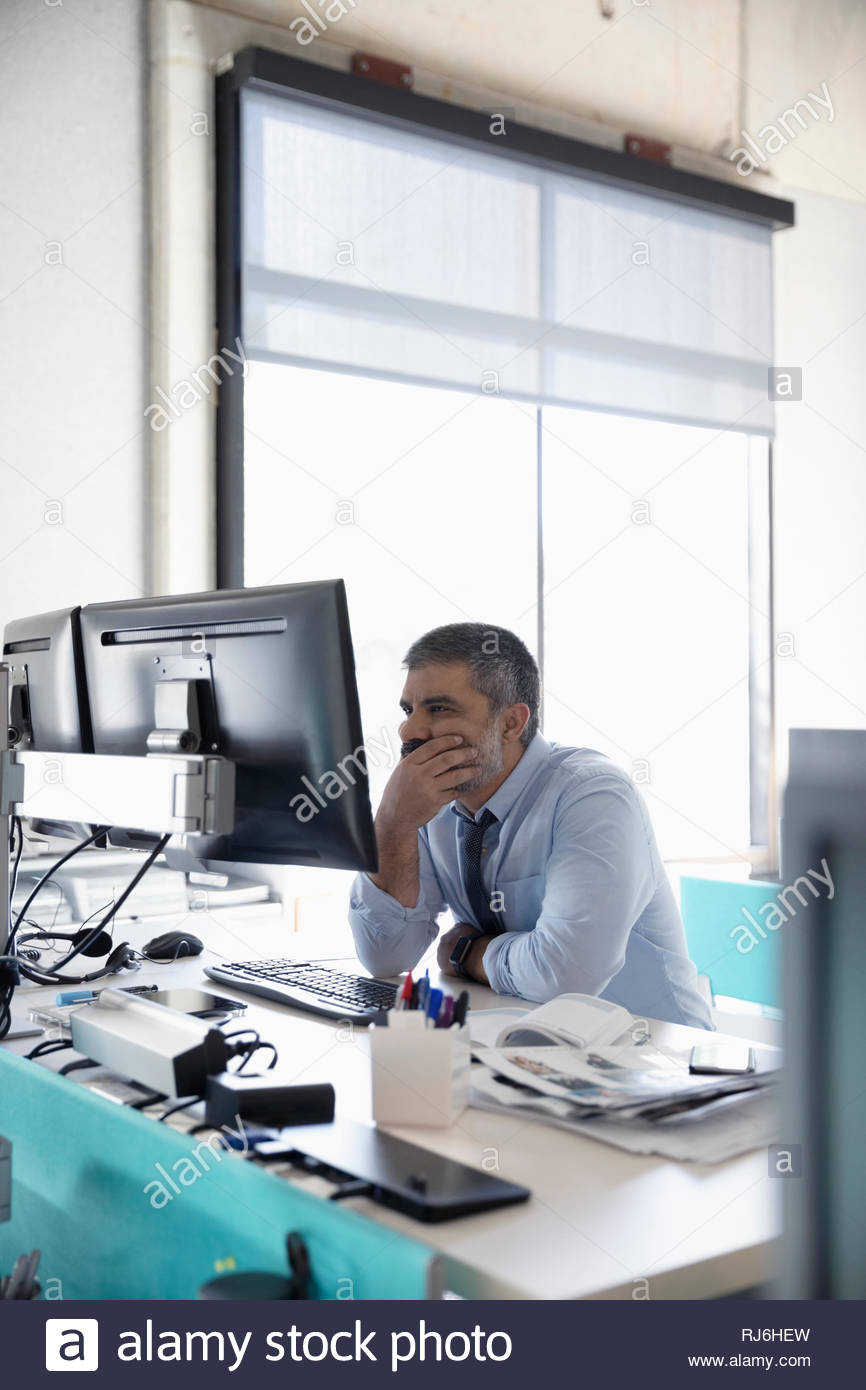 Focused businessman working at computer in office - Stock Image
