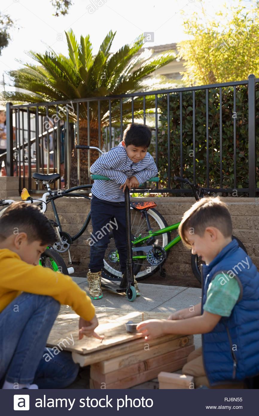 Latinx boys building bike ramp - Stock Image