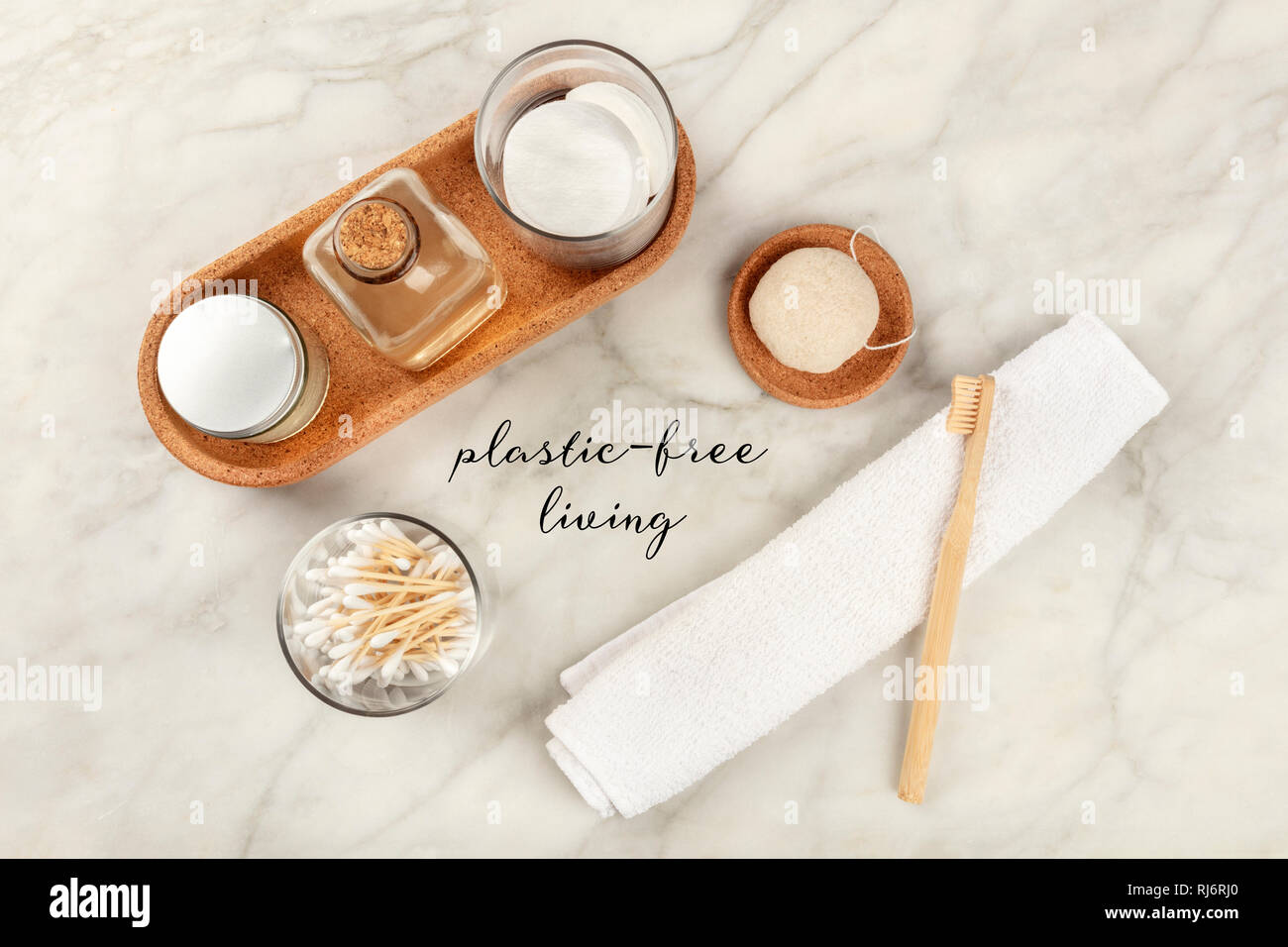 Plastic-free living. An overhead photo of sustainable toiletries. Homemade lotions, bamboo toothbrush, natural Konjac sponge, and biodegradable bamboo - Stock Image