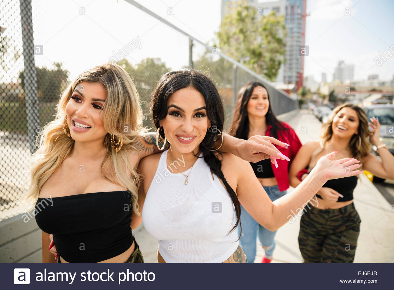 Portrait carefree Latinx young women walking on urban overpass - Stock Image