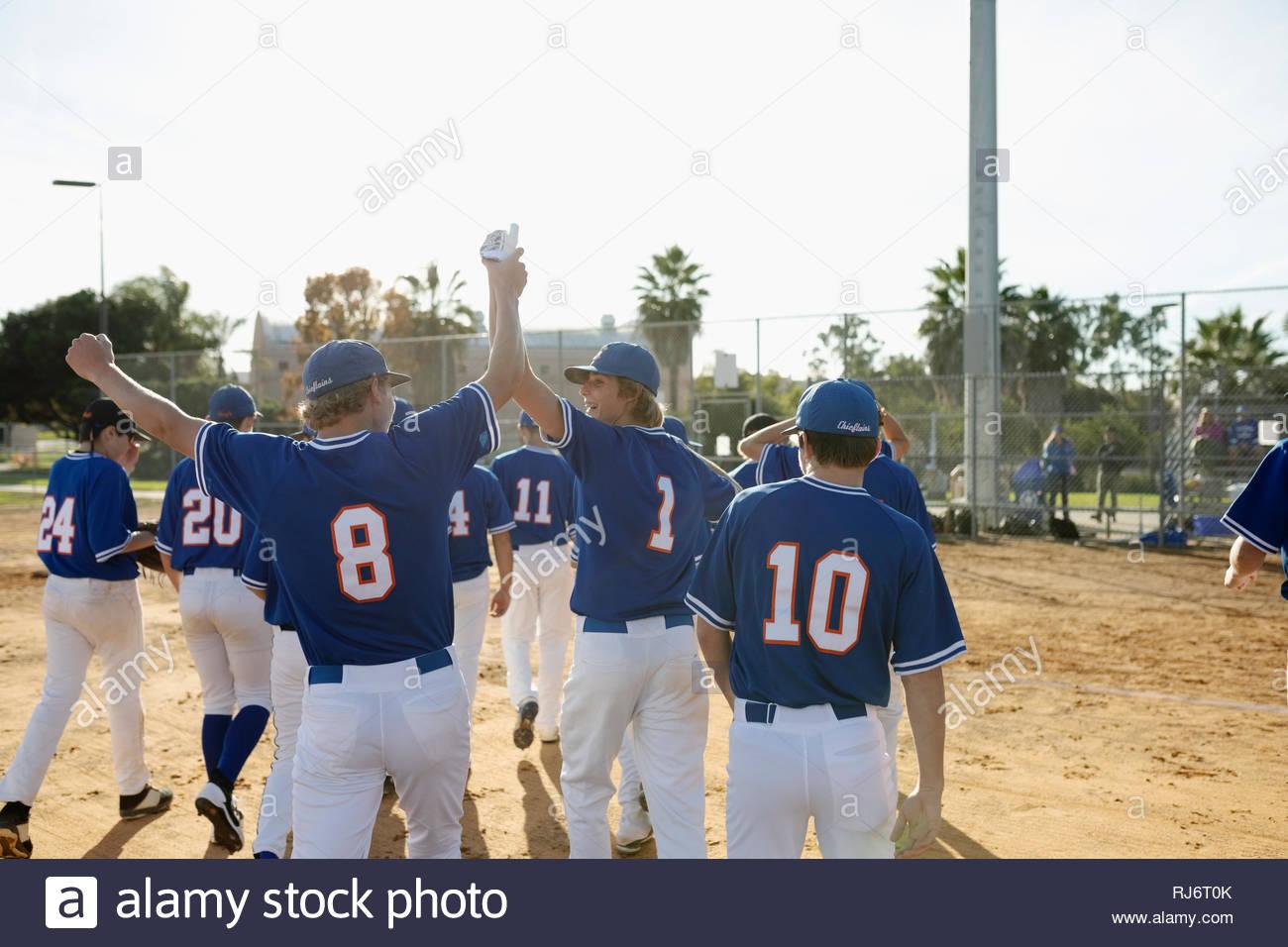 Baseball players cheering, walking off sunny field - Stock Image