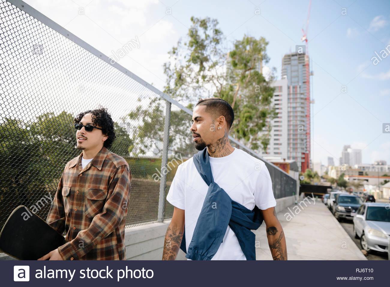 Latinx young men with skateboard walking on urban sidewalk - Stock Image