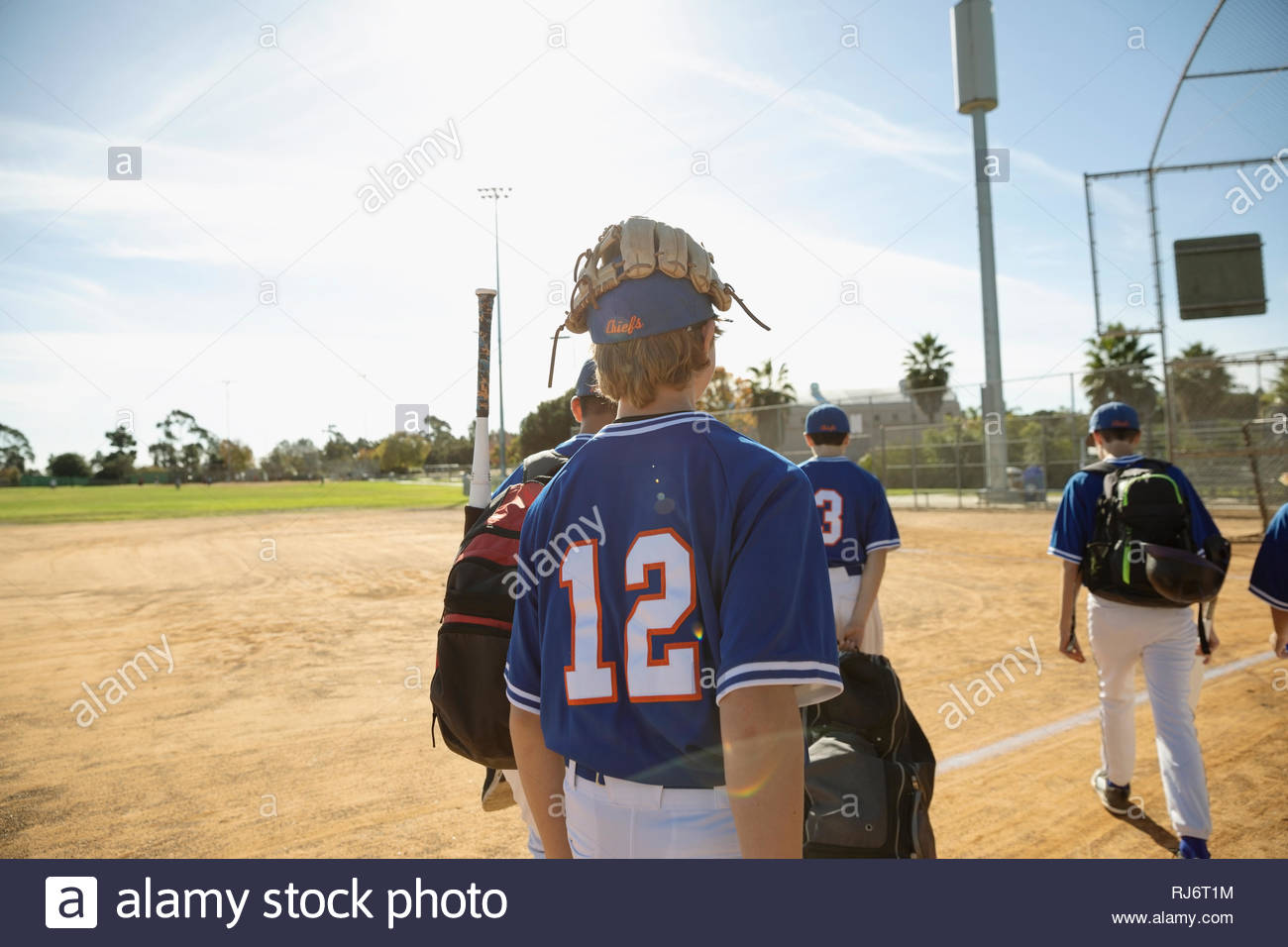 Baseball players walking off sunny field - Stock Image