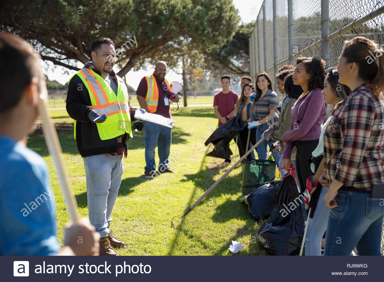 Man in reflective vest leading meeting for volunteers cleaning sunny park - Stock Image