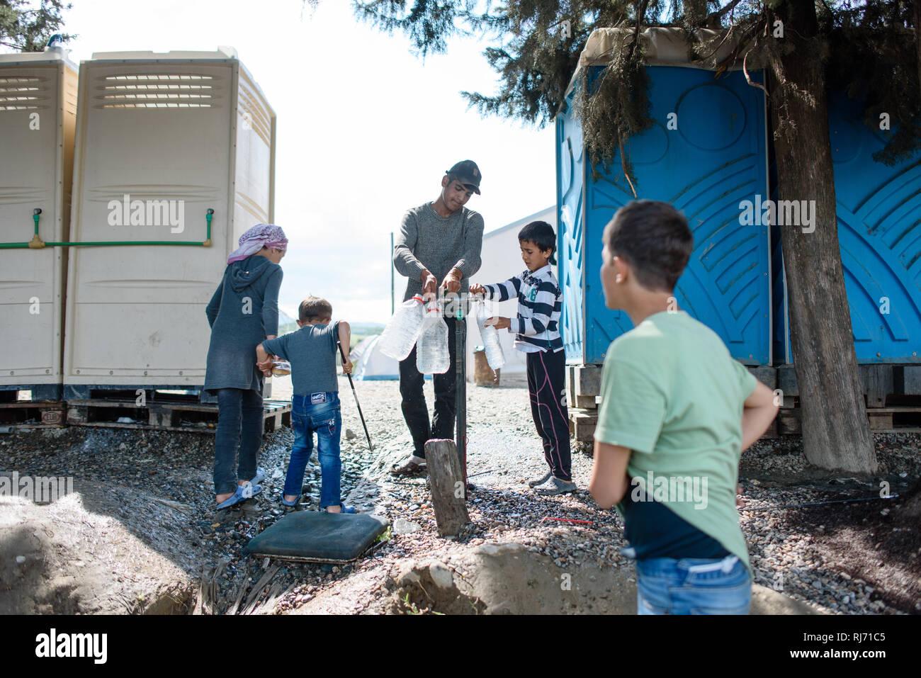 Menschen füllen sich Trinkwasser ab. Flüchtlingscamp von Idomeni in Griechenland an der Grenze nach Mazedonien, April 2016. - Stock Image