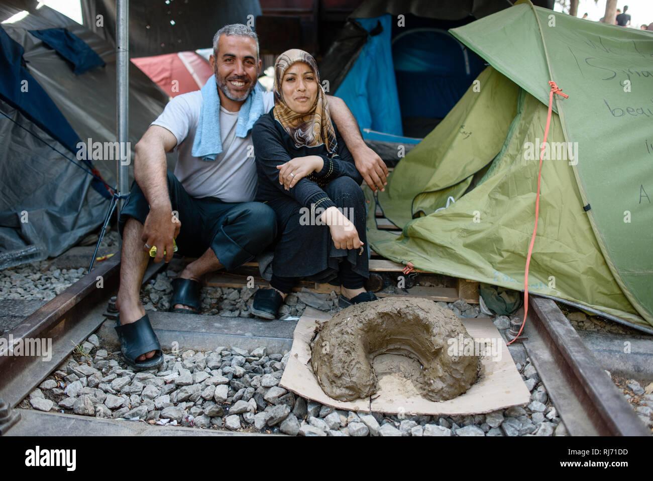 Ein Ehepaar aus Syrien im Flüchtlingscamp von Idomeni in Griechenland an der Grenze nach Mazedonien, April 2016. Dieses Gebilde im Vordergrund ist ein - Stock Image