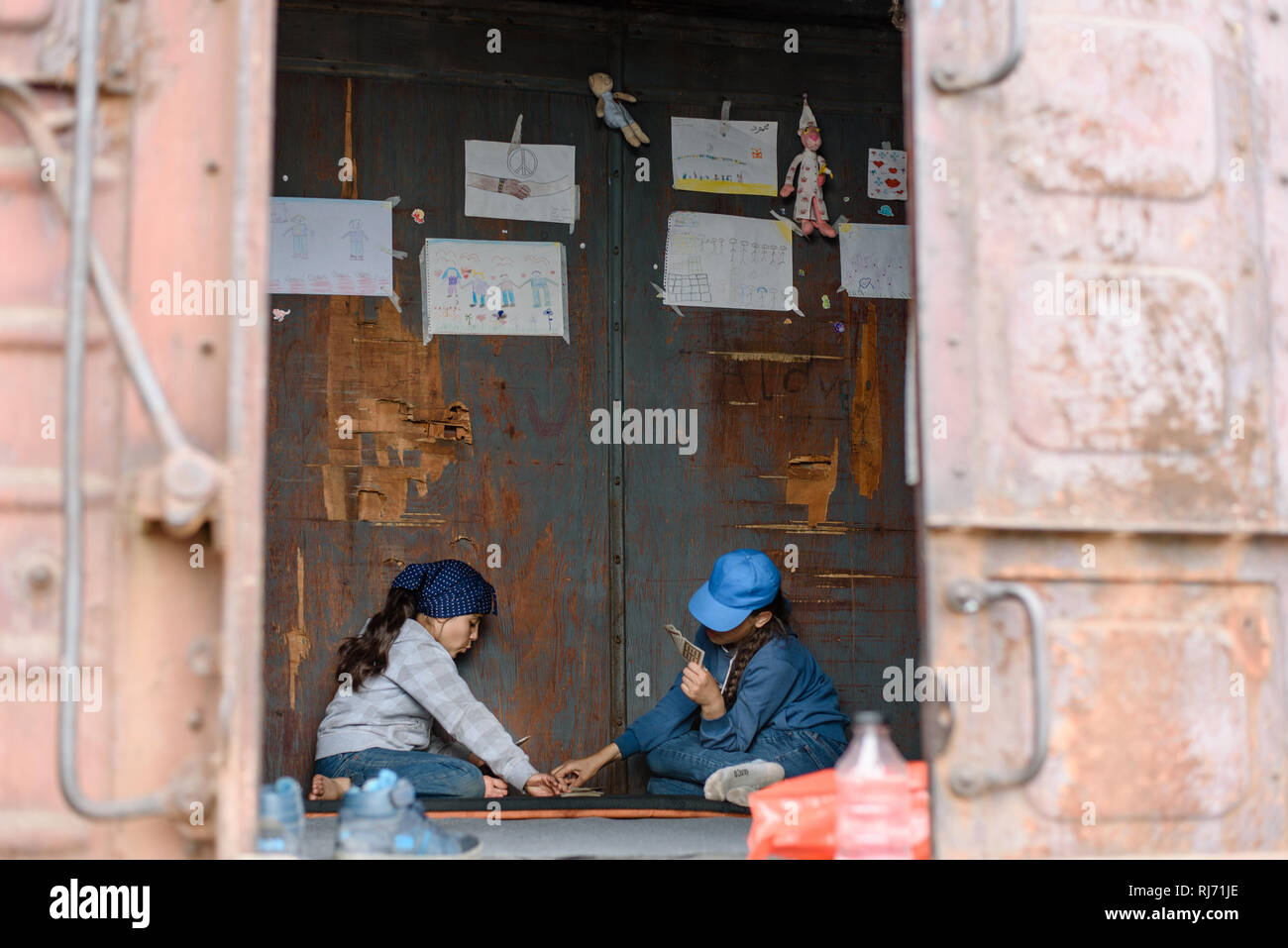 Zwei Schwestern spielen Karten um das ganze Chaos zu vergessen welches draussen herrscht. Flüchtlingscamp in Idomeni in Griechenland an der Grenze nac - Stock Image