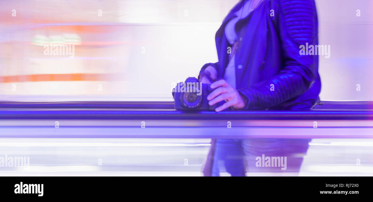 Frau mit Fotoapparat auf Transportband, Detaol, Oberkörper, - Stock Image