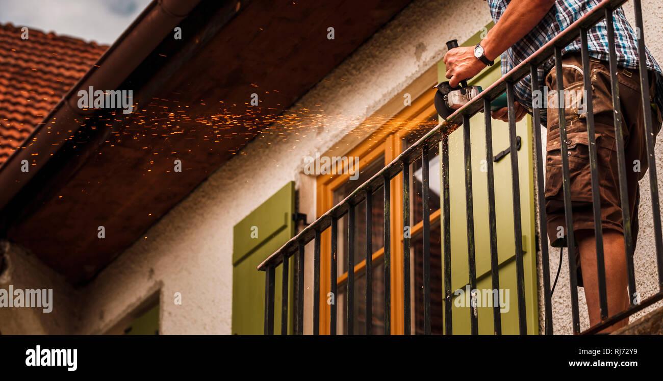 Renovierung - ein Handwerker schneidet mit der Flex den alten Balkon weg, - Stock Image