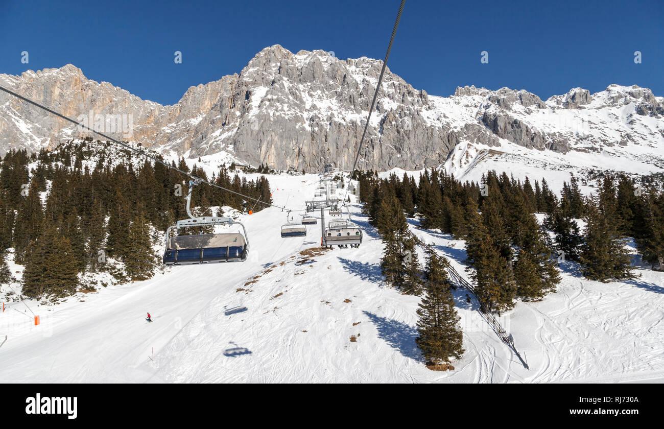 Wintersport in traumhafter Bergkulisse, Gondeln eines Sessellifts, - Stock Image