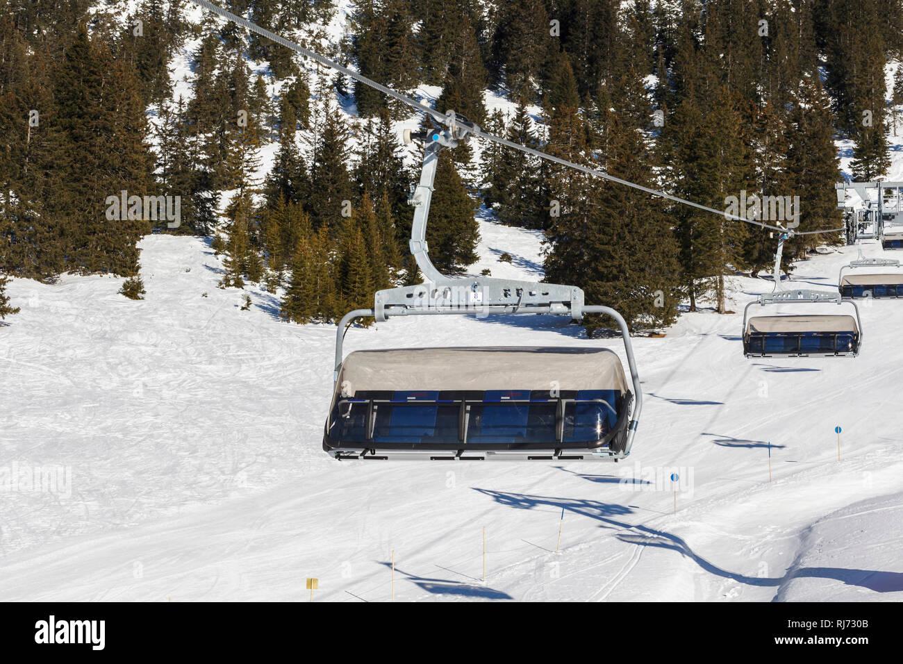 Wintersport in traumhafter Bergkulisse, leere Gondeln eines Sessellifts, - Stock Image