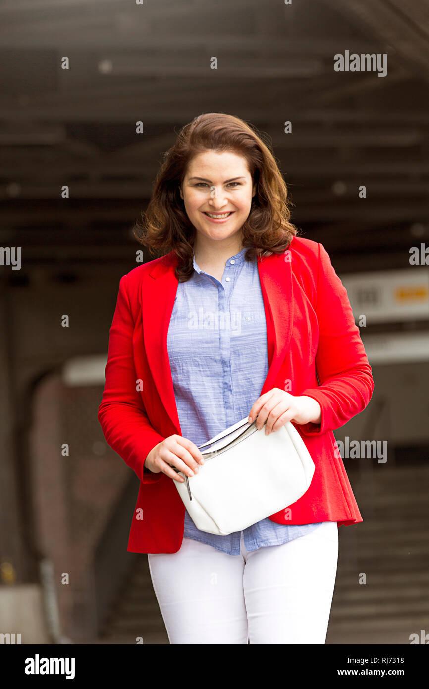 Frau, lächeln, Handtasche, halten, Blick Kamera, - Stock Image