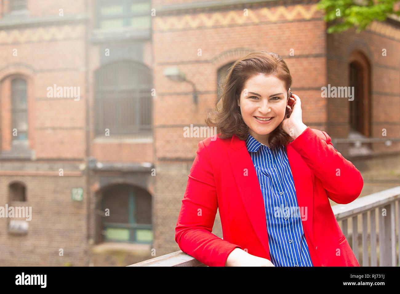 Frau, lächeln, Blazer, rot, Geländer, anlehnen, Halbporträt, - Stock Image