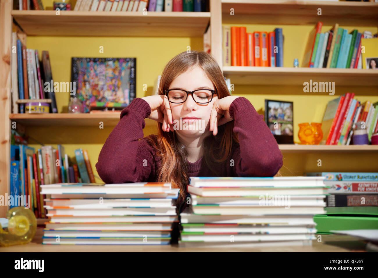Mädchen, 10 Jahre alt, ermüdet von den Hausaufgaben, vor einem Stapel Bücher, mit geschlossenen Augen - Stock Image